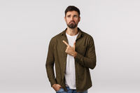 Man regret missed good opportunity feeling sad and miserable. Upset young bearded guy pulling gloomy face, frowning and look depressed, pointing upper left corner, standing white background