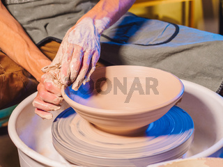 Creating earthenware and traditional pottery concept. Experienced male potter's hands creating beautiful clay product - bowl - using professional tools. Toned cinematic, craft factory authentic