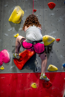 Young girl climbing up on practice wall in indoor rock gym