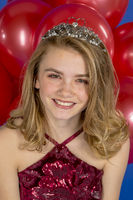 Lovely Blonde Teenage Model Posing In A Dress And Tiara Against Red Balloons In A Studio Environment