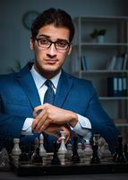 Businessman playing chess in strategy concept