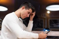 Frustrated caucasian young man reading message with disappointing news on digital smartphone.