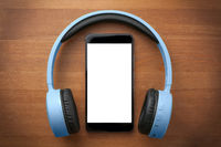 Pair of blue headphones around a blank screen smartphone on orange wooden table
