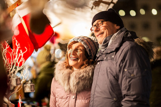 senior couple at christmas market souvenir shop