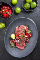 Traditional South American barbecue wagyu roast beef sliced with pico de gallo and salsa verde garnished as top view in a modern design plate