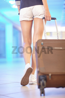 The girl in shorts walks around the airport hall and carrying a suitcase