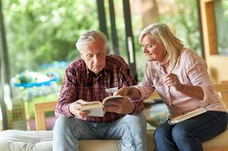 Senioren Paar im Wohnzimmer beim Buch lesen