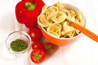 Tortellini mit Tomatensoße vor weißem Hintergrund
