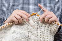 Close up of hands knitting warm sweater