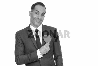 Mature happy Persian businessman holding red heart ready for Valentine's day