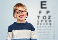 little boy in glasses showing tongue