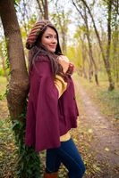 Beautiful girl smiling at the camera, in stylish autumn fashion clothes, in park scenery with trees and leaves. Gorgeous romantic young woman outdoors. Full length shot, retouched, vibrant colors