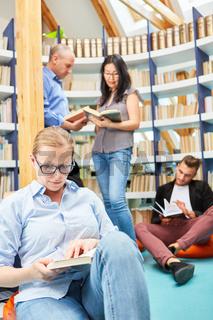 Gruppe Leute bei Buch lesen in Bibliothek