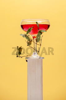 Red drink in a glass on a wooden pedistale.