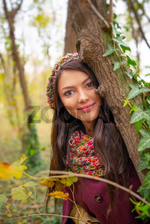 Beautiful girl smiling at the camera, in stylish autumn fashion clothes, in park scenery with trees and leaves. Gorgeous romantic young woman outdoors. Close-up portrait, retouched, vibrant colors