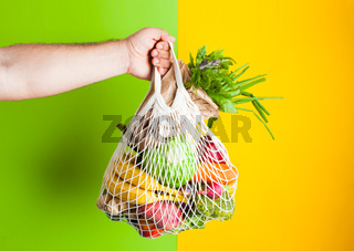 Cotton bag full of vegetables on yellow background