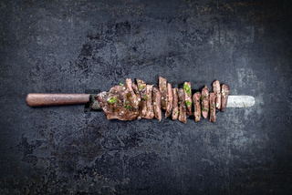 Traditional barbecue skirt steak sliced as close-up on a knife with copy space