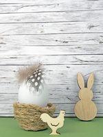 Ostern Hintergrund mit Osterei, Osterhase und Hahn auf grün vor Holz