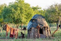 old himba woman in front of hut, Namibia Africa