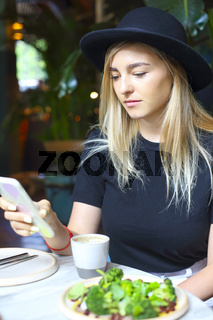 Attractive cute Caucasian blond girl in white jeans skirt, blouse and black hat looking  at the mobile phone