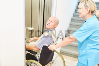Pflegekraft schiebt Senior Mann im Rollstuhl