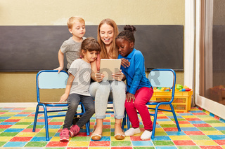 Lehrerin liest aus einem Ebook vor im Kindergarten