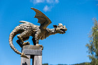 Profile view of bronze dragon statue on pole isolated on blue sky