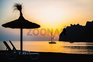 Mediterranean Sunrise off the Mountainous Coast of Mallorca in the Ballearic Islands with Silhouetted Sailboat and Beach Umbrella
