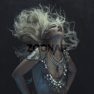 beautiful woman with silver scales on the man as a dragon armor, with the hair in the wind in sensual poses on rustic gray background