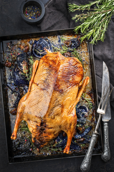 Traditional roasted stuffed Christmas duck with blue kraut as top view on a board
