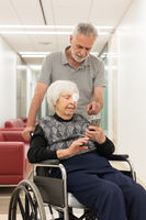 Middle aged man showing and helping elderly 95 years old woman sitting at the wheelchair how to use modern mobile phone.