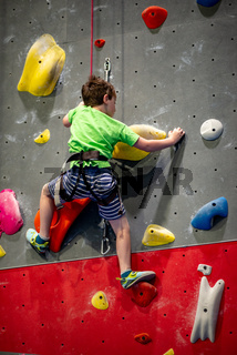 Young boy climbing up on practice wall in indoor rock gym