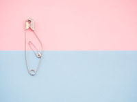 A safety pin representing a pregnant woman with a baby
