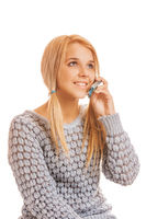 Beautiful smiling young woman in gray sweater talking on a mobile phone
