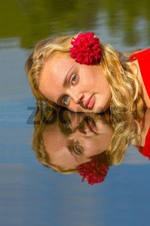 Portrait mirror image blonde woman in water
