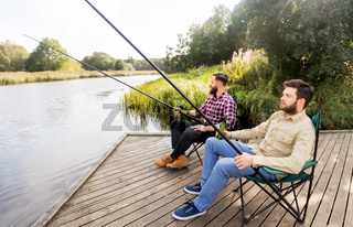 male friends fishing and drinking beer on lake
