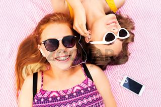teenage girls listening to music from smartphone