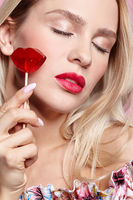 Blonde woman with eyes closed with candy. Red female lips shape lollipop. Sweet tooth concept