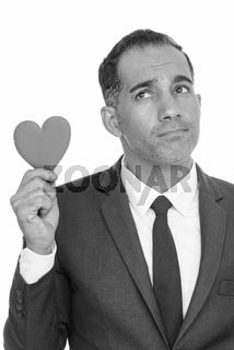 Mature happy Persian businessman holding red heart while thinking