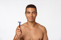 Close up of a happy naked african man holding razor isolated over gray background.