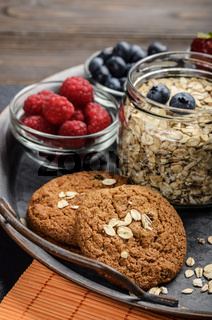 Tray with ripe organic bilberry raspberry strawberry oat cookies and almonds set on slate closeup