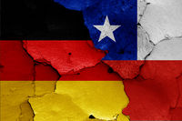 flags of Germany and Chile painted on cracked wall