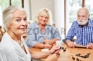 Ehrgeizige Seniorin spielt mit Freunden Domino