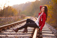 A gorgeous romantic young woman seated down on the railroad tracks, smiling and looking away from the camera, in fall scenery outdoors. Fashion concept portrait in beautiful autumn natural light