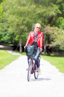 Happy young woman riding a bicycle in the park.