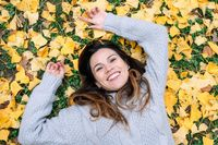 woman smiling, lying over leaves at the park in autumn time, top view.