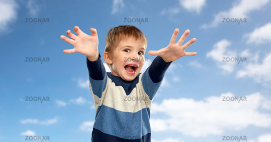 little boy making scary faces over sky background