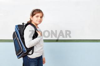 Mädchen als Schulanfänger mit Schulranzen in Schule