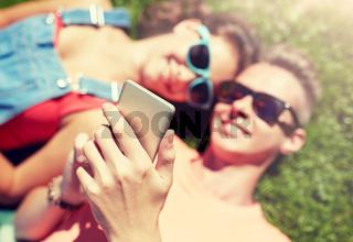 happy teenage couple smartphone lying on grass
