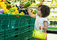 Child shopping peppers in supermarket. Concept for buying fruits and vegetables
